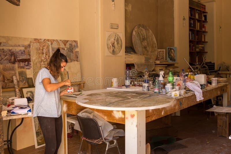 Spello, Umbrië, Italië, 31 Juli, 2017: Een jong wijfje in haar studio die aan een groot rond kunststuk werken stock fotografie