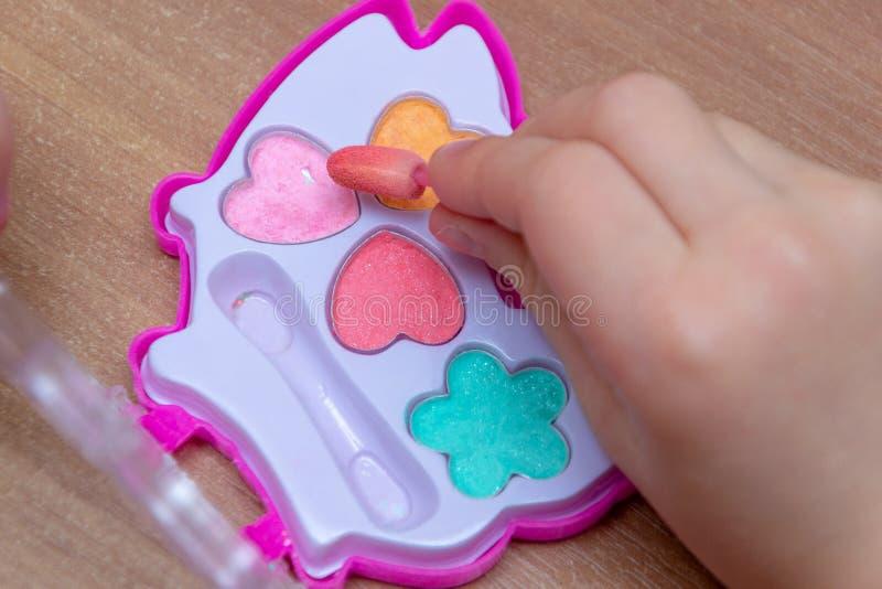 spelmeisjes in schoonheidsmiddelen schoonheidsmiddelen voor meisjes, mom& x27; s kosmetische toebehoren in daughter& x27; s ruimt stock foto's