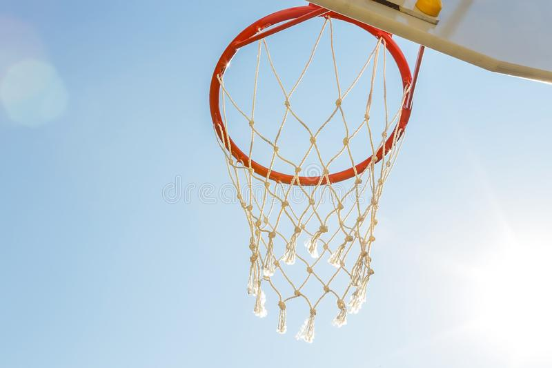 Spelsporten, competities Teamsporten, openluchtvrije tijd, actieve recreatie, vermaak Basketbalhoepel met netto tegen blauw royalty-vrije stock foto