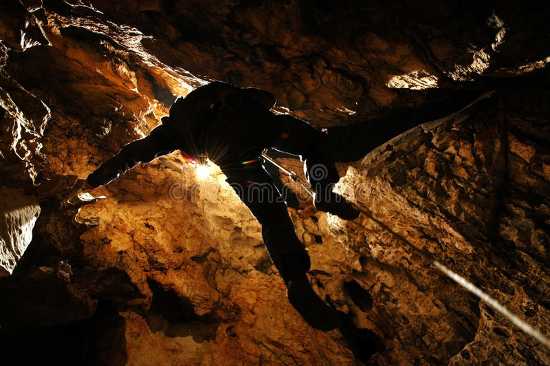 Spelunker abseiling in a pothole. Spelunker abseiling on a rope in a pothole royalty free stock images