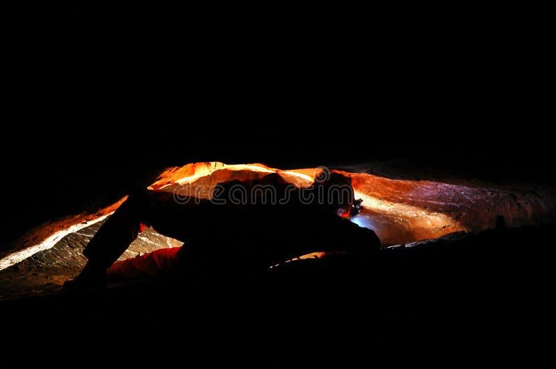 Spelunker, der eine schmale Höhle erforscht stockfotos