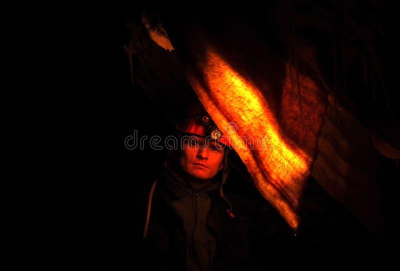Spelunker, der in einer Höhle sich wundert lizenzfreie stockfotografie