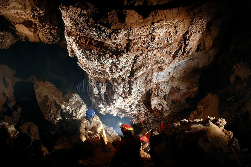 Spelunker, der schöne Stalaktiten in einer Höhle bewundert lizenzfreie stockfotos