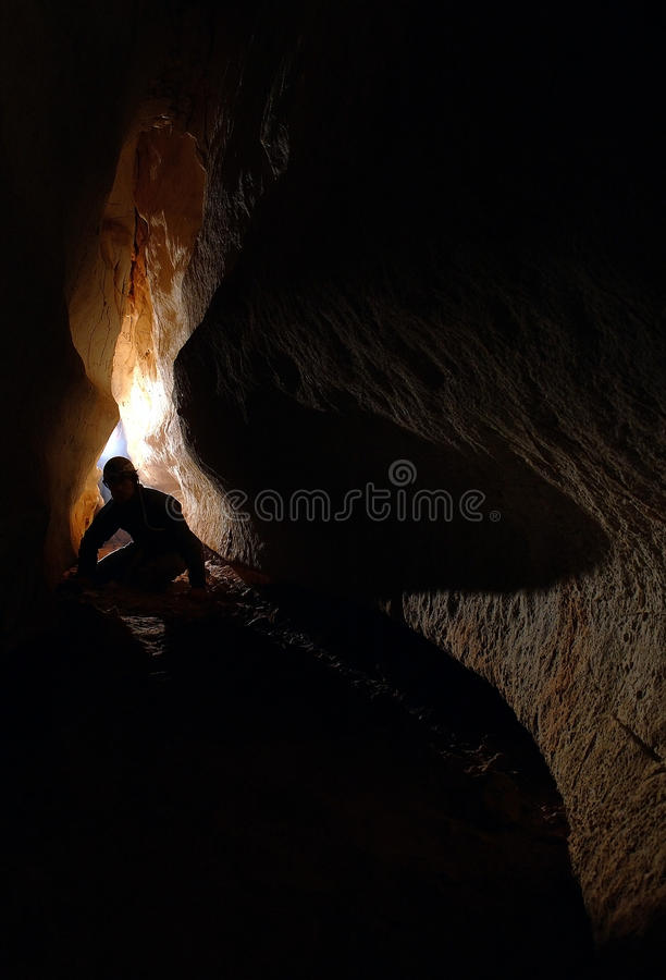 Spelunker exploring a cave royalty free stock photo
