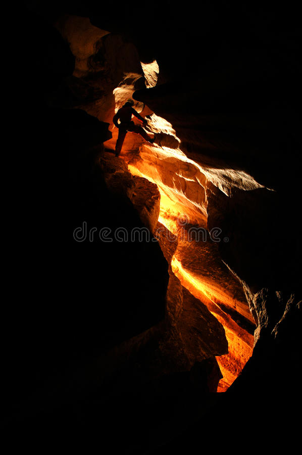 Spelunker exploring a cave stock photography