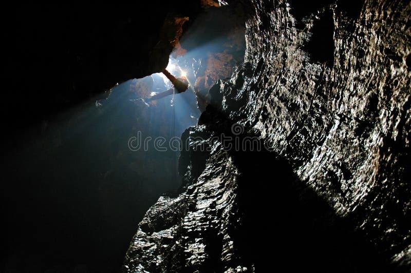 Spelunker que abseiling em uma caverna fotografia de stock royalty free