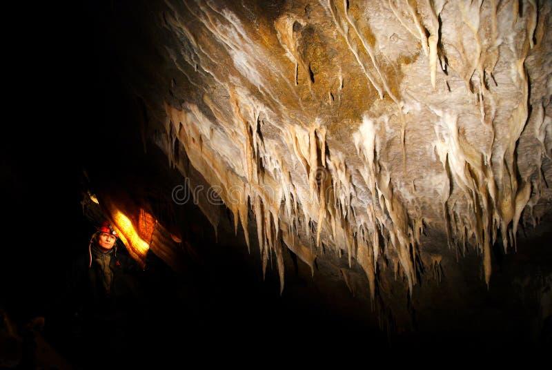 Spelunker que admira estalactites em uma caverna fotografia de stock