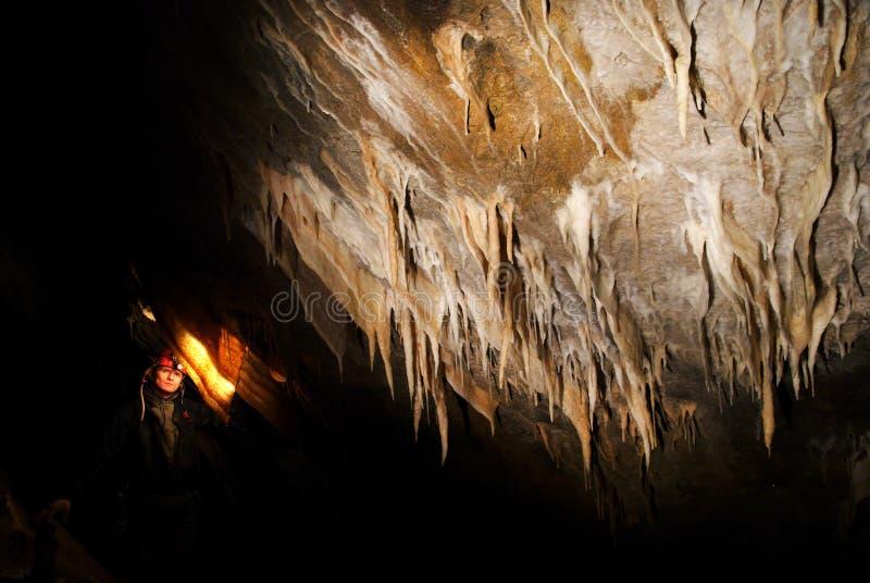 Spelunker que admira estalactites na caverna imagens de stock