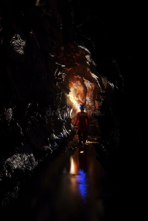 Spelunker que explora uma caverna imagens de stock royalty free