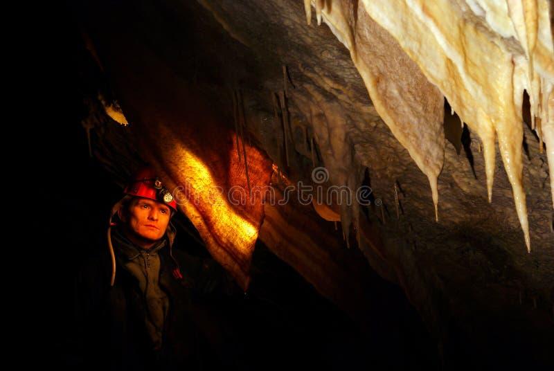 Spelunker som beundrar stalaktit i en grotta arkivbild