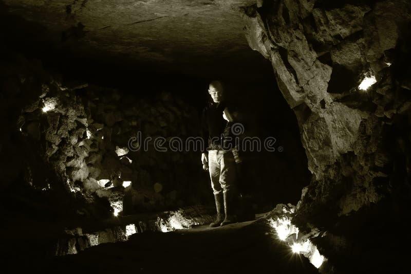 Spelunkers die in kamer in verlaten mijn in Wiltshire, UKMan en kind zich ondergronds in een verlaten mijn bevinden stock foto