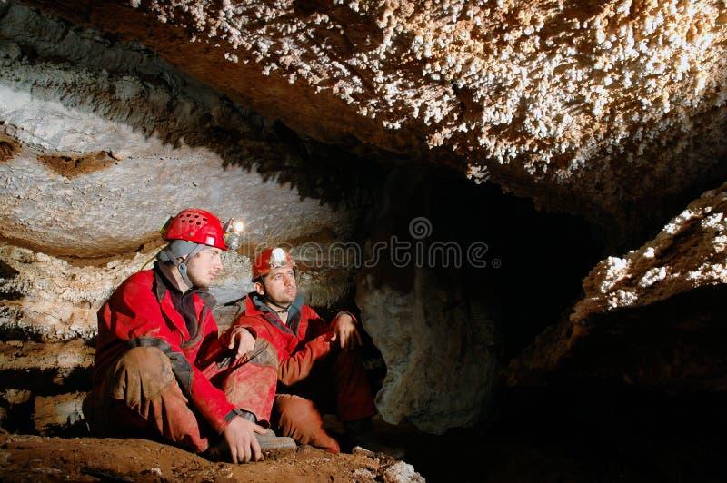 Spelunkers i en grotta royaltyfri fotografi