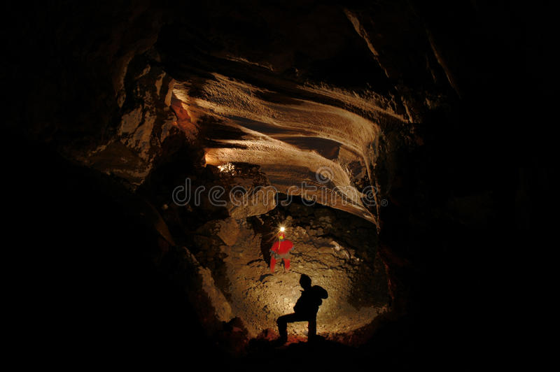 Spelunkers que exploram uma caverna subterrânea foto de stock