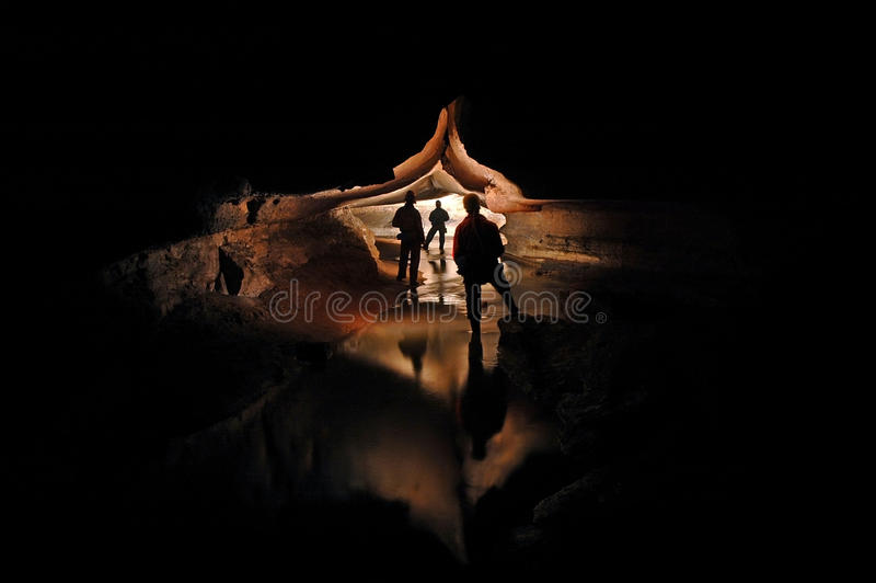 Spelunkers que exploran un río subterráneo de la cueva imagen de archivo libre de regalías