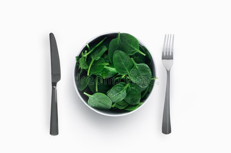 Spenat på den vita plattan med kniven och gaffel på vit bakgrund äta för begrepp som är sunt royaltyfri foto
