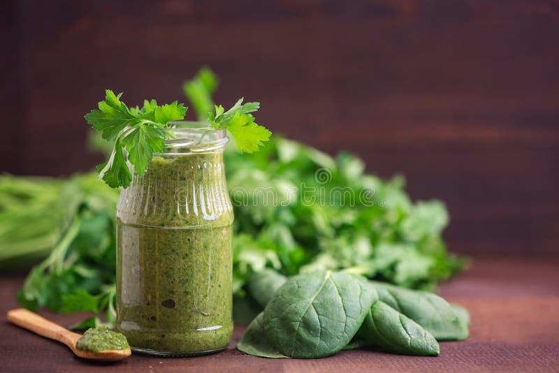 Spenatsmoothies Sund grön fruktsaft med ingredienser på den mörka trätabellen Slapp fokus royaltyfria foton