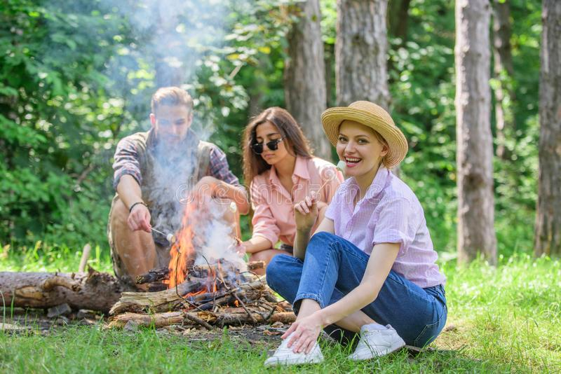 Spend great time on weekend. Company friends prepare roasted marshmallows snack nature background. Roasting marshmallows. Popular group activity around bonfire stock image
