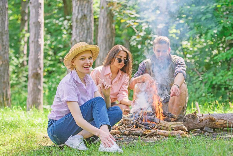 Spend great time on weekend. Company friends prepare roasted marshmallows snack nature background. Roasting marshmallows. Popular group activity around bonfire royalty free stock images