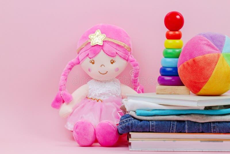 Spende, Nächstenliebekonzept Angefüllte weiche Puppe, Baby, das Ringe Pyramide stapeln, Kinderkleidung und Bücher über rosa Hinte stockfotos