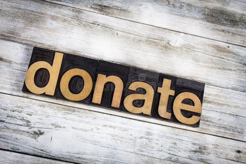 Spenden Sie Briefbeschwerer-Wort auf hölzernem Hintergrund lizenzfreies stockfoto