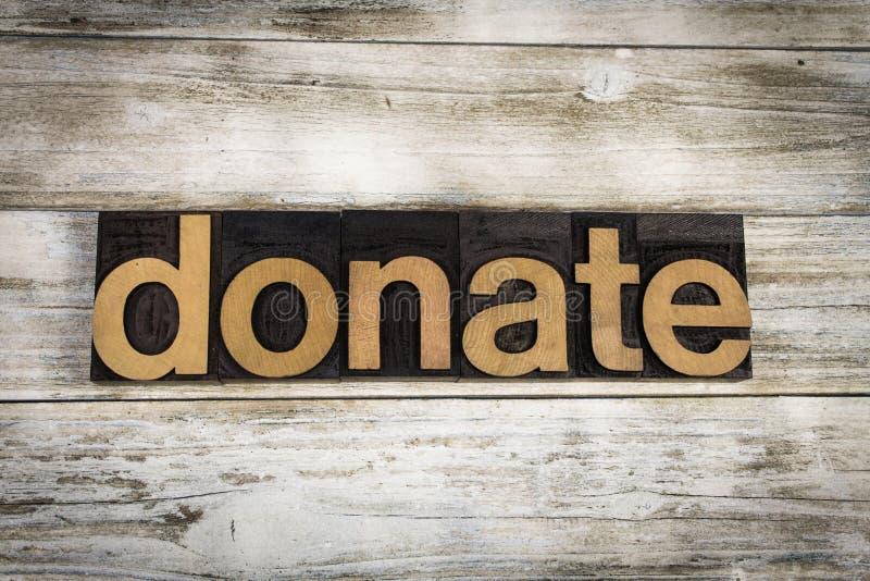 Spenden Sie Briefbeschwerer-Wort auf hölzernem Hintergrund lizenzfreies stockbild
