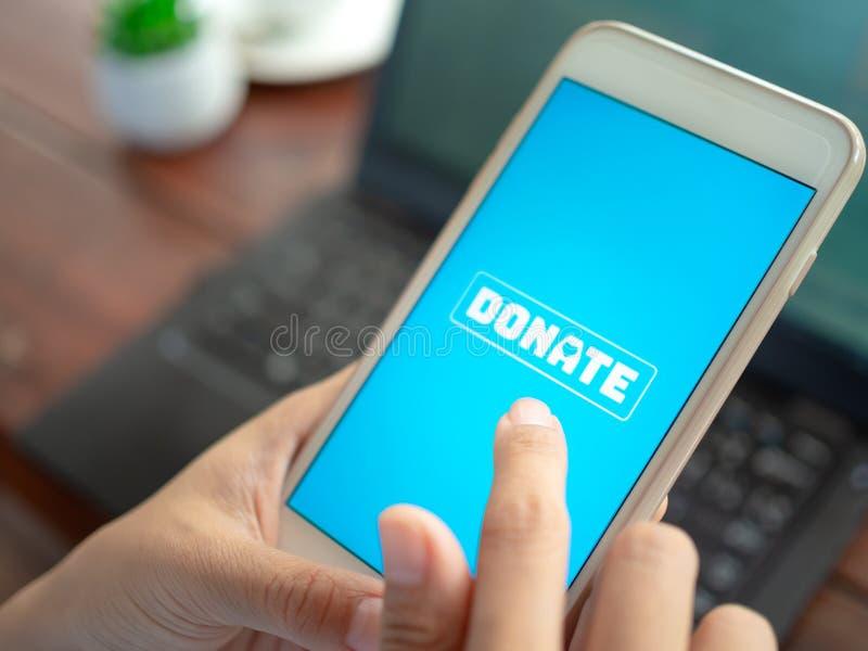 Spendengeld online durch Smartphone lizenzfreies stockbild