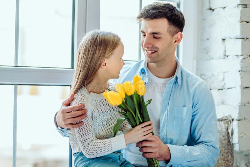 Spendera någon kvalitets- tid med min farsa Fadern ger hennes dotter en bukett av tulpan royaltyfria foton