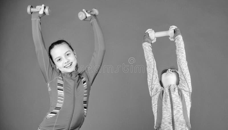 Spendera timmar p? idrottshallen Gulliga systrar som g?r idrottshallkondition?vningar med hantlar Sport och kondition f?r ungar l royaltyfria bilder