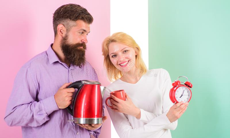 Spending good morning together. Electric kettle boils water very quickly. Prepare favourite drink in minutes. Modern. Devices make our life easier. Couple stock images