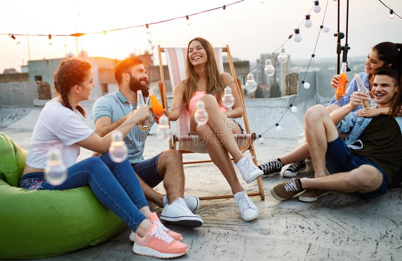 Spending great time with friends. Young friends chatting and havinf fun on the roof of the building stock images