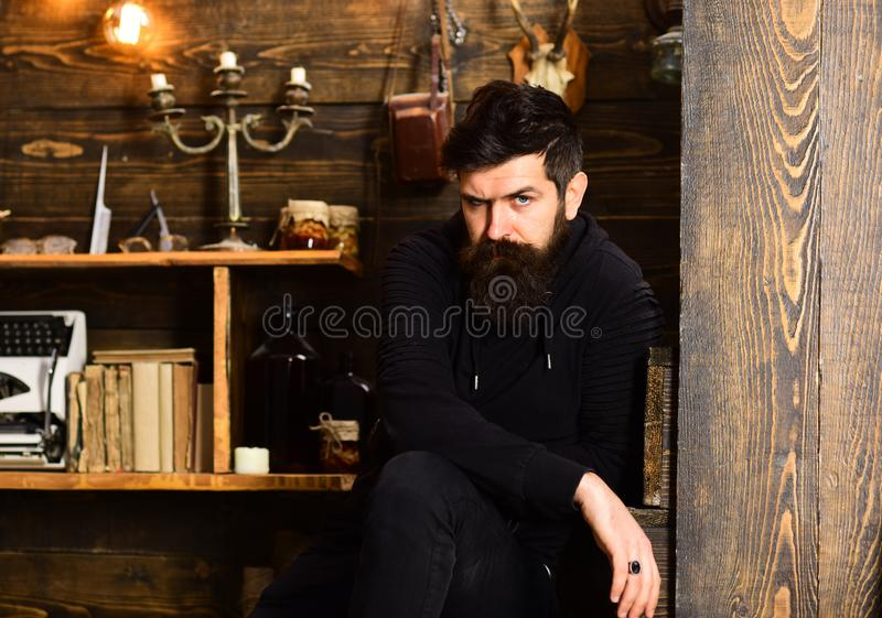 Spending great time at home. Man with beard looks strictly. Man bearded enjoy evening, wooden background. Guy in cozy stock photo