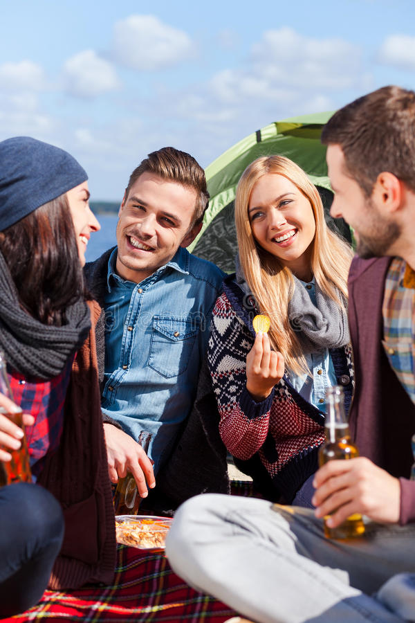 Spending great time together. Group of young cheerful people drinking beer and talking while camping at the riverbank royalty free stock photos