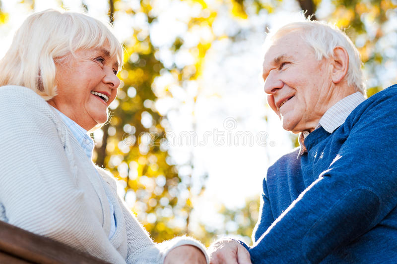 Spending great time together. Low angle view of happy senior couple looking at each other and smiling while standing outdoors royalty free stock images