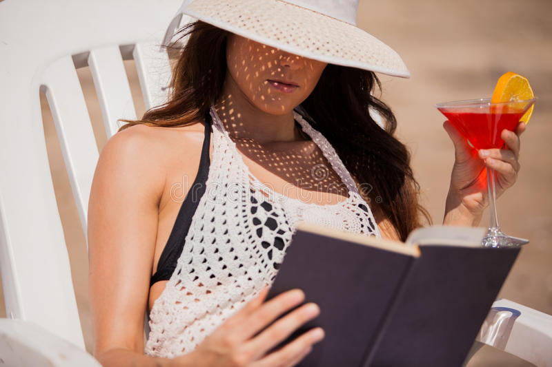 Spending holidays at the beach. Pretty Hispanic young woman reading a book and drinking a martini at the beach stock photo