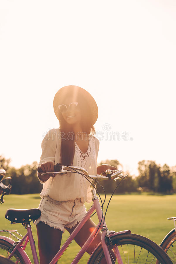 Spending nice time on fresh air. Beautiful young woman in fedora pushing her bicycle and smiling royalty free stock images