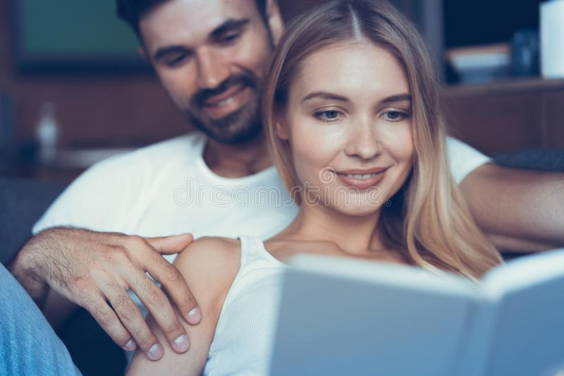 Spending nice time at home. Beautiful young loving couple bonding to each other and smiling while woman holding a book. stock photography
