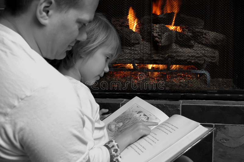 Spending time with Family. Father reads bedtime stories to his daughter in front of a glowing firelight. They are black and white and the fire is in color