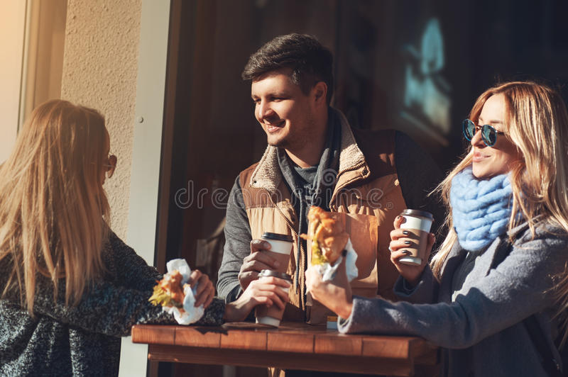 Spending time with friends. Group of cheerful young people talking to each other while eating croissant and sandwiches stock photography