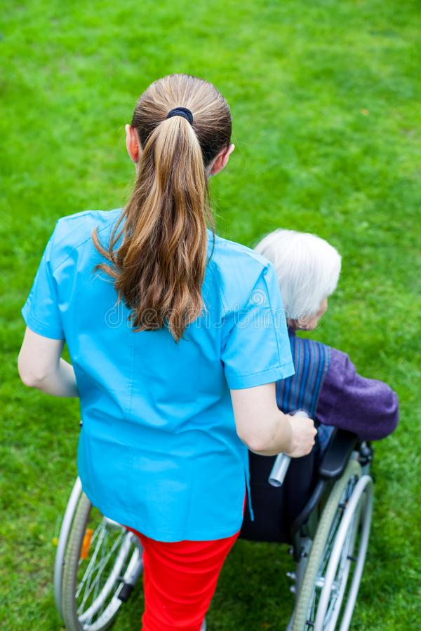 Spending time outdoor with caregiver. Caregiver spending time outdoor with handicapped senior woman, home care - back view stock images