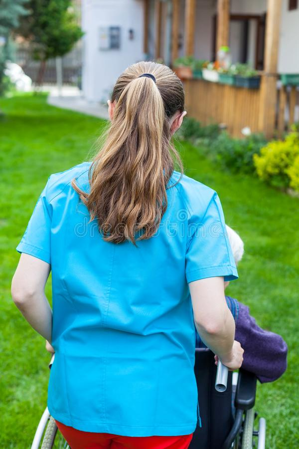 Spending time outdoor with caregiver. Caregiver spending time outdoor with handicapped senior woman, home care - back view royalty free stock image