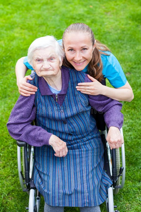 Spending time outdoor with caregiver. Portrait of elderly disabled woman sitting in a wheelchair spending time outdoor with cheerful young caregiver stock photo