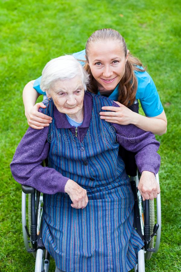 Spending time outdoor with caregiver. Portrait of elderly disabled woman sitting in a wheelchair spending time outdoor with cheerful young caregiver royalty free stock photos