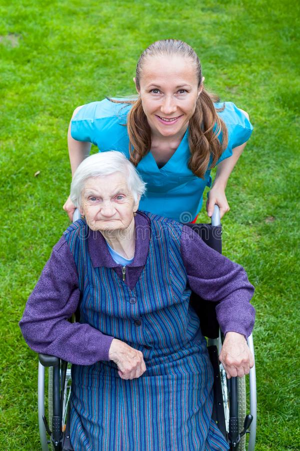 Spending time outdoor with caregiver. Portrait of elderly disabled women sitting in a wheelchair spending time outdoor with cheerful young caregiver royalty free stock photo