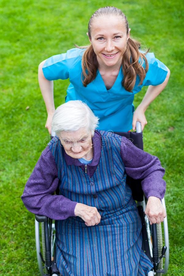 Spending time outdoor with caregiver. Portrait of elderly disabled women sitting in a wheelchair spending time outdoor with cheerful young caregiver stock image