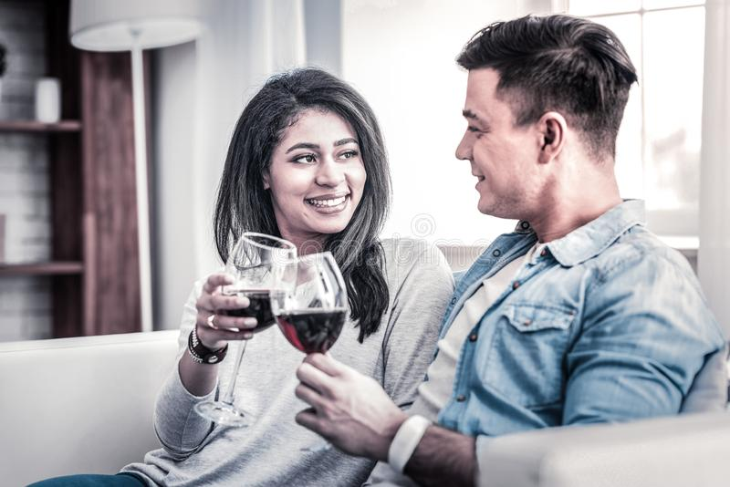 Openly smiling African American woman clinking wine glasses royalty free stock photos