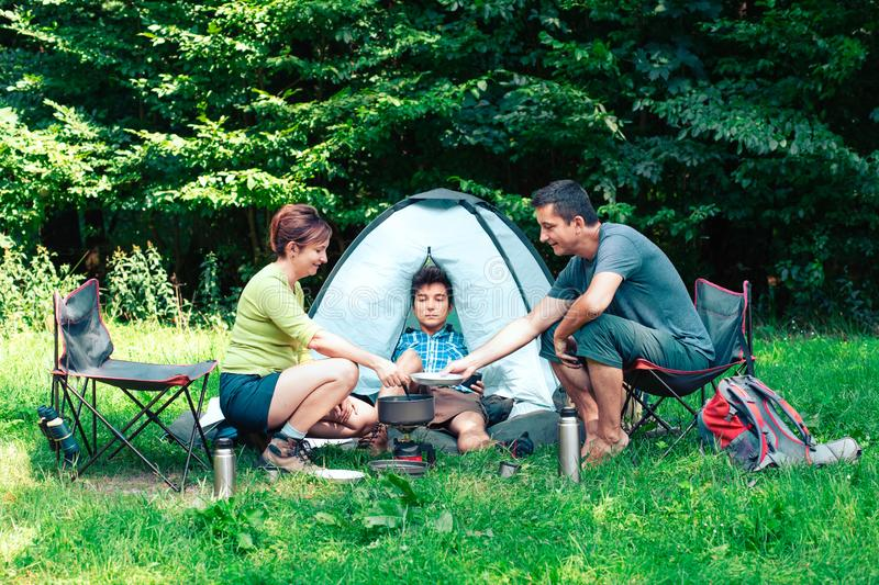 Spending a vacation on camping. Preparing a meal outdoor next to tent stock image