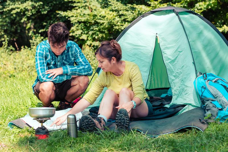 Spending a vacation on camping. Preparing a meal outdoor. Planning next trip stock image