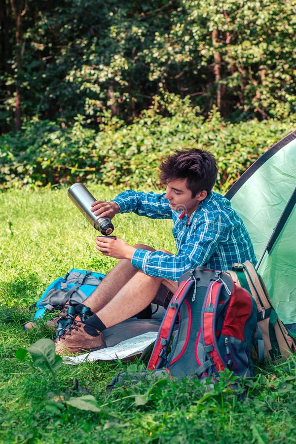 Spending a vacation on camping. Preparing a meal outdoor. Young man planning next trip and drinking a coffee stock images