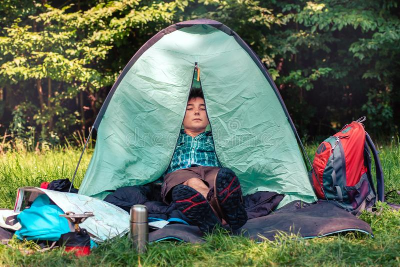 Spending a vacation on camping. Young man resting in a tent stock photo