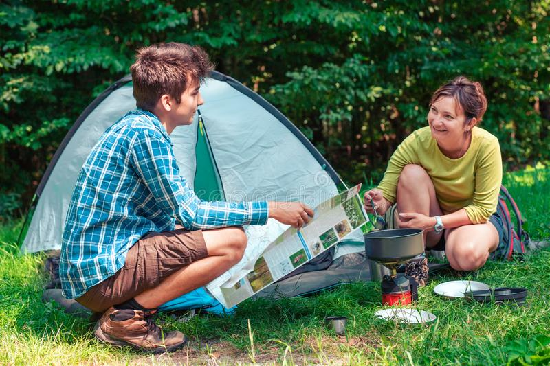 Spending a vacation on camping. Woman preparing a meal outdoor. Man holding a map. Planning next trip stock photography